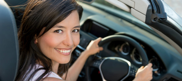 beautiful woman smiling while riding her car hire