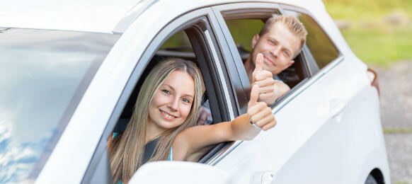 couple giving two thumbs up on their rental car