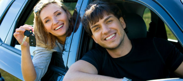 couple smiling inside their hire car