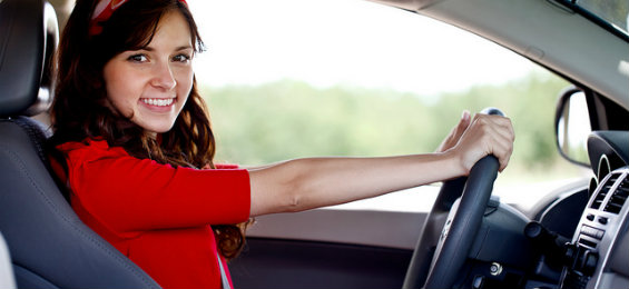Cheerful girl driving her own car