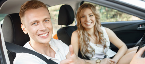 smiling couple inside their car