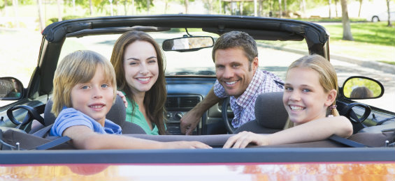 Cheerful family riding a convertible car