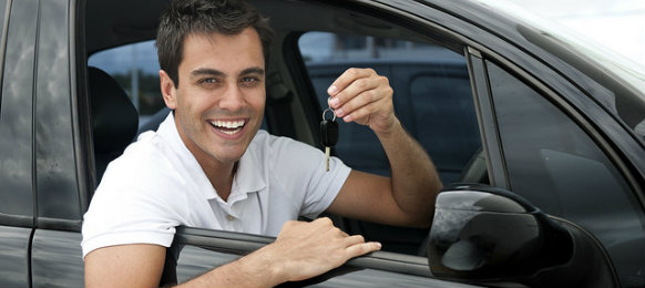smiling guy holding his car rental key