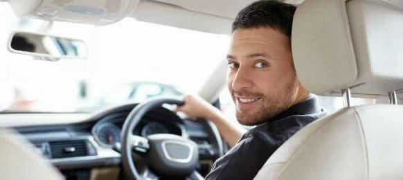 smiling man driving a car rental