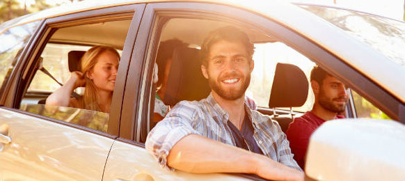 man driving a car rental with his friends