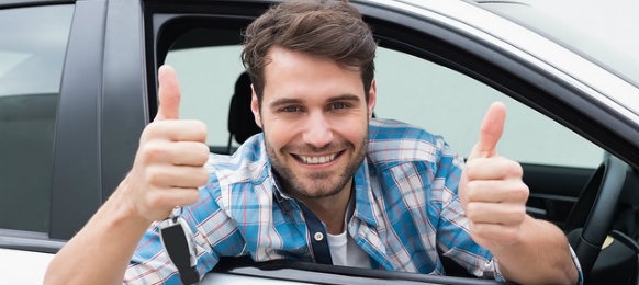 male guy giving a thumbs  up from his car rental