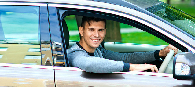 smiling man while driving a car hire