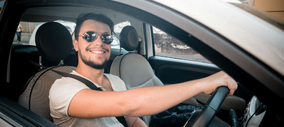 man wearing sunglasses driving his rental car
