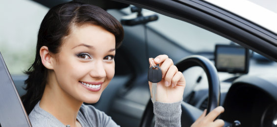 Woman driving a car while showing her car key