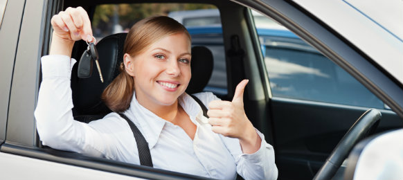 woman holding car hire key while showing thumbs up