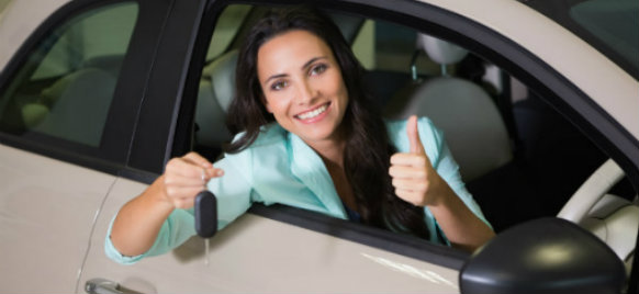 woman holding car key and doing a thumbs up