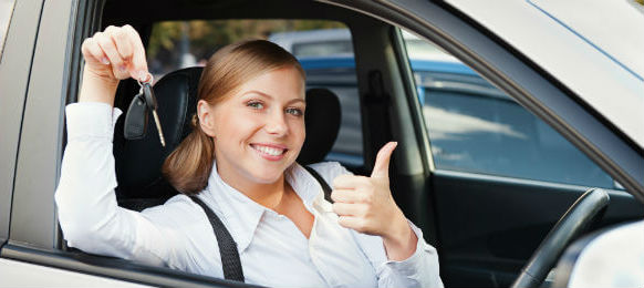 woman driving a car rental and giving it a thumbs up
