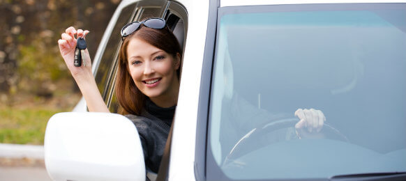 woman driving a white car hire while holding keys