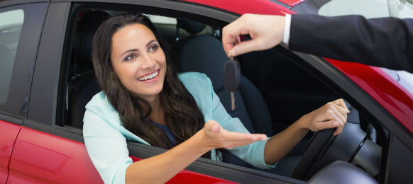 woman getting the key to her red rental car