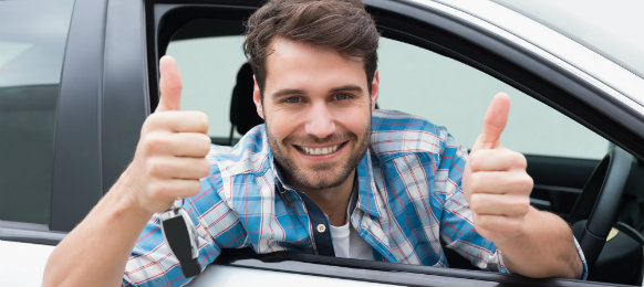 happy guy giving a thumbs up sign inside his new car